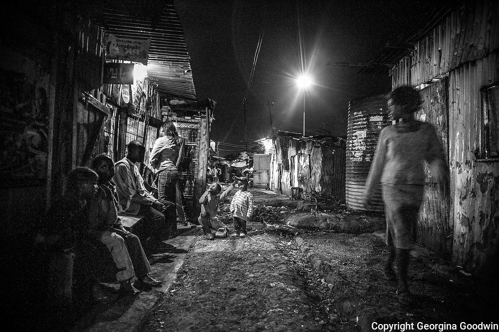 Night scene at the top end of Kawangware Street, the most notorious street for rapes. Since the installation of the flood light further down in December 2012, a joint initiative of the Kenya Government and Safaricom who pay the electricity fee, the incidences of rape have been reduced. <br /> This image is from a series focusing on and around the rape and the women victims that occur every half a day in Mugumoini Village in Nairobi's Southlands, a slum home to 20,000 people in abject poverty with little or no income, with the aim of creating exposure and empowerment for change. ©GGoodwin