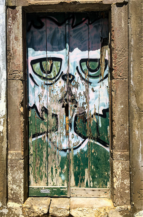A doorway painted with street art of a cat, in poor condition.