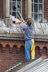 © Licensed to London News Pictures . 14/09/2015. Manchester, UK. STUART HORNER smashes window panes on the roof at HMP Manchester (formerly Strangeways Prison ) , where Horner is conducting a rooftop protest against prison conditions . Photo credit : Joel Goodman/LNP