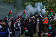 """Leicester, United Kingdom, May 24, 2021: A man holds a flare during a protest outside an Israeli owned weapons factory known as Elbit UAV, where people gathered to support the """"Palestine Action"""" activists who had occupied the building for six consecutive days. Multiple members of the public were arrested by the police after they tried to provide food and water to activists standing on the rooftop of the building on the same day. (Photo by Vudi Xhymshiti)"""