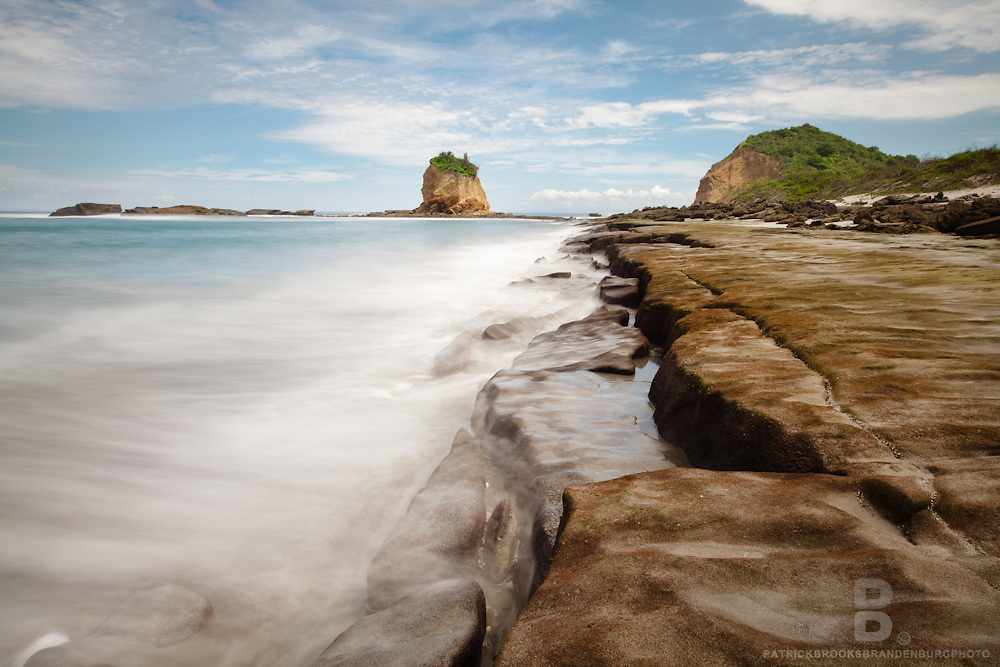 The beautiful and pristine Tortuguita Beach just north of Los Frailes Beach in the protected Ecuadorian Machalilla National Park shows a rock shelf reef at low tide in this llong exposure landscape.