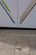 Apple iPhone ad and bent fashion retailer hanger dropped on a central London side street.