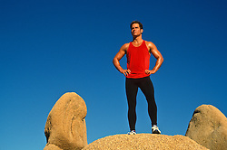 Jogger standing on a rock formation in Joshua Tree, California