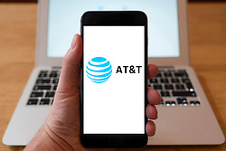 Using iPhone smartphone to display logo of AT&T the American multinational telecommunications conglomerate