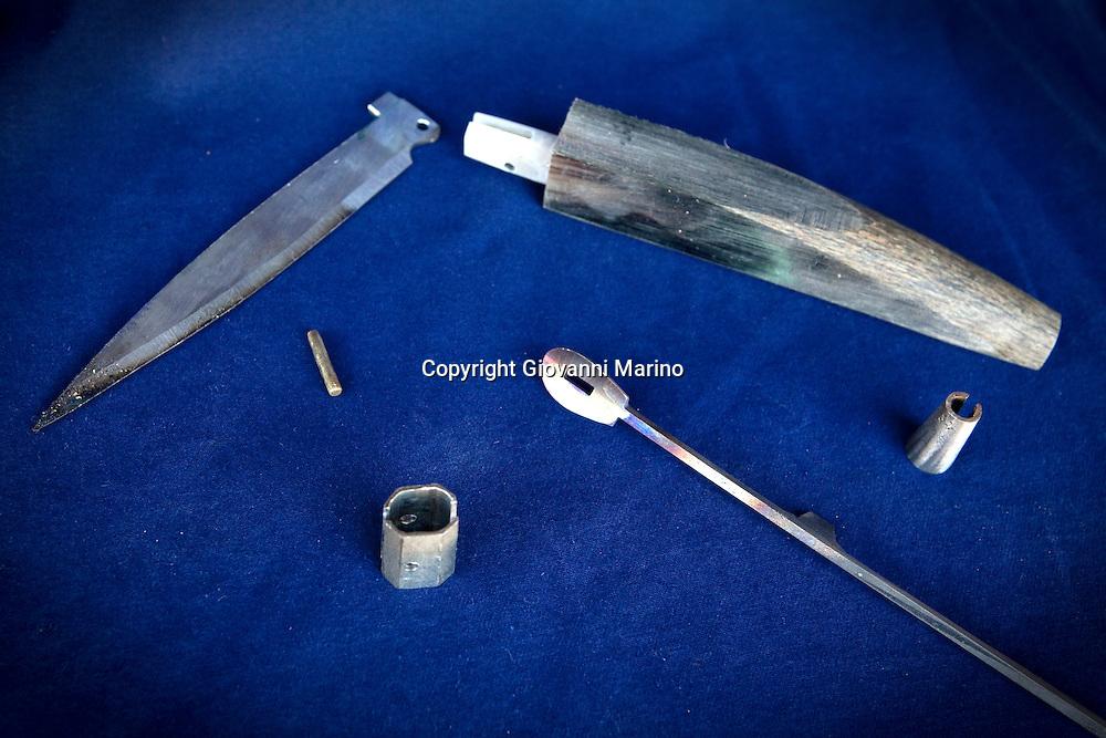 """Avigliano (PZ), 04-10-2010 ITALY - Vito Aquila, artigiano di Balestre. Il coltello di Avigliano, comunemente conosciuto come """"balestra"""", impreziosito con decorazioni in argento e ottone che le conferivano un certo valore non solo artistico,ha identificato per tutto l'Ottocento e parte del Novecento il carattere fiero e risoluto del popolo aviglianese, come attestato in una lunga casistica di riscontri documentari. La """"balestra"""" è un'arma a tutti gli effetti, ed è già considerata -nell'ambito delle manifatture di ferro - oggetto di pregio. Per l'approvvigionamento dell'argento e dell'ottone destinati alla decorazione del manico del coltello gli armieri si rivolgevano agli orefici o agli ottonari. La """"balestra"""" era un'arma del popolo, pronta ad essere impiegata, a seconda delle circostanze, per la difesa o l'offesa tanto dagli uomini quanto dalle donne. Queste, la ricevevano come regalo di fidanzamento dal rispettivo promesso sposo per meglio difendere il proprio onore, perpetrando un'usanza molto sentita almeno fino ai primi decenni del '900..Nella Foto: Balestra smontata."""