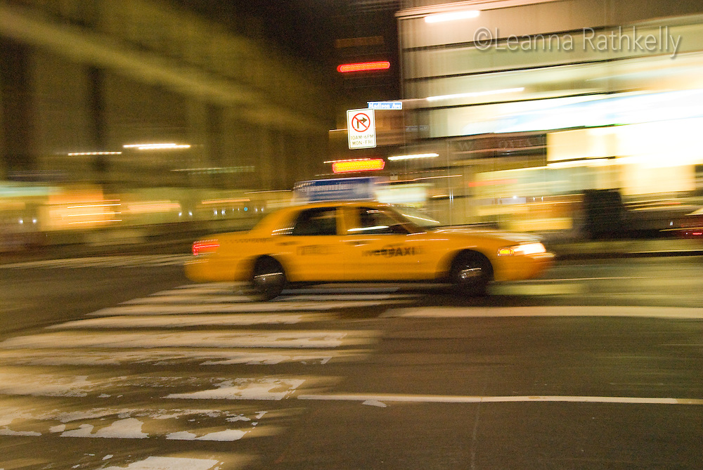 A taxi cab speeds by in New York City, NY, USA
