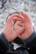 Brad Lautenschlager peers through his cupped hands, looking at the camera, on a snowy Winter day in Boulder, Colorado.