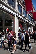 Shoppers walk past Sale signs on Regent Street in central London. It's time for the summer sales, and most shops are advertising big reductions in prices. Bargains are avaiable and the shopping streets are busy.