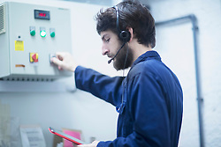 Young male engineer wearing headset and updating control panel using digital tablet in an industrial plant, Freiburg im Breisgau, Baden-Wuerttemberg, Germany