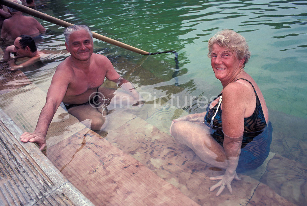 A middle-age husband pours thermal healing spa waters on to his wife in Budapests famous Szechenyi thermal bath, on 18th June 1990, in Budapest, Hungary. Budapest is especially known for its spas. The Széchenyi Medicinal Bath  Szechenyi-gyogyfurdo is the largest medicinal bath in Europe. Its water is supplied by two thermal springs, their temperature is 74°C/165°F and 77°C/171°F, respectively. The bath can be found in the City Park, and was built in 1913 in Neo-baroque style to the design of Gyozo Czigler.
