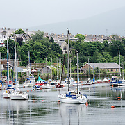 Sailboats moored in the foreground, with Caernarfon township in the background on the banks of the River Seiont.