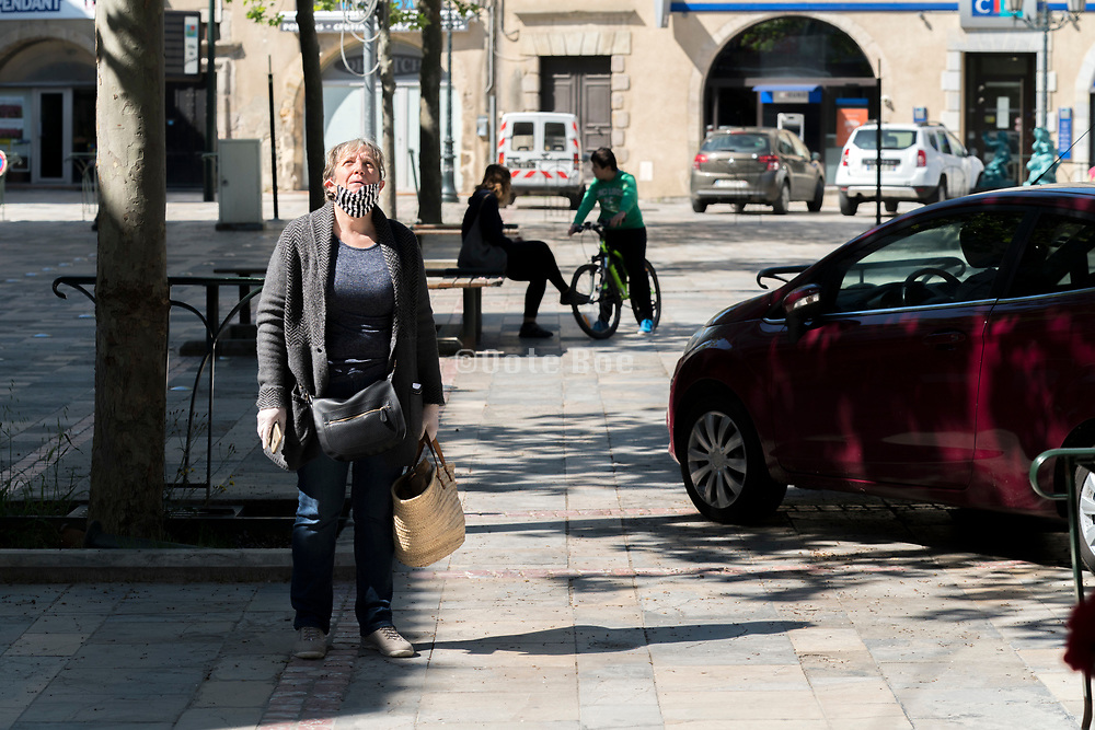 woman in the street talking to a person in apartment window during Covid 19 crisis and lockdown France Limoux April 2020
