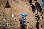 Palma de Mallorca, Mallorca, Worker with a blue parasol is renovating the Església de Sant Miquel.