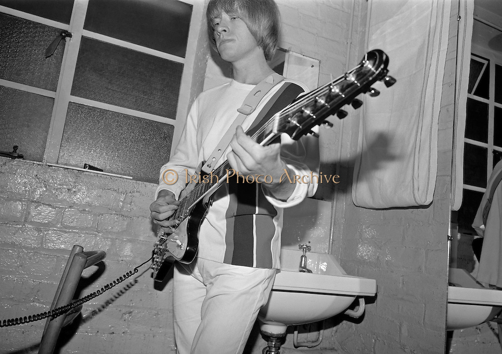 .The Rolling Stones Charlie is my Darling - Ireland 1965 -..Brian Jones of The Rolling Stones checks the tuning on his guitar in his dressing room before going on stage at the Adelphi Theatre, Middle Abbey Street, Dublin. This was the band's second Irish tour of 1965...The Rolling Stones Charlie is my Darling - Ireland 1965.Out November 2nd from ABKCO.Super Deluxe Box Set/Blu-ray and DVD Details Revealed. ..03/09/1965..09/03/1965..03 September 1965...ABKCO Films is proud to join in the celebration of the Rolling Stones 50th Anniversary by announcing exclusive details of the release of the legendary, but never before officially released film, The Rolling Stones Charlie is my Darling - Ireland 1965.  The film marked the cinematic debut of the band, and will be released in Super Deluxe Box Set, Blu-ray and DVD configurations on November 2nd (5th in UK & 6th in North America).. .The Rolling Stones Charlie is my Darling - Ireland 1965 was shot on a quick weekend tour of Ireland just weeks after ?(I Can't Get No) Satisfaction? hit # 1 on the charts and became the international anthem for an entire generation.  Charlie is my Darling is an intimate, behind-the-scenes diary of life on the road with the young Rolling Stones featuring the first professionally filmed concert performances of the band's long and storied touring career, documenting the early frenzy of their fans and the riots their live performances incited.. .Charlie is my Darling showcases dramatic concert footage - including electrifying performances of ?The Last Time,? ?Time Is On My Side? and the first ever concert performance of the Stones counterculture classic, ?(I Can't Get No) Satisfaction.?  Candid, off-the-cuff interviews are juxtaposed with revealing, comical scenes of the band goofing around with each other. It's also an insider's glimpse into the band's developing musical style by blending blues, R&B and rock-n-roll riffs, and the film captures the spark about to combust into The Greatest Rock and R