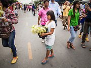 """22 JULY 2013 - PHRA PHUTTHABAT, THAILAND: A girl walks among the crowd selling flowers during the Tak Bat Dok Mai at Wat Phra Phutthabat in Saraburi province of Thailand, Monday, July 22. Wat Phra Phutthabat is famous for the way it marks the beginning of Vassa, the three-month annual retreat observed by Theravada monks and nuns. The temple is highly revered in Thailand because it houses a footstep of the Buddha. On the first day of Vassa (or Buddhist Lent) people come to the temple to """"make merit"""" and present the monks there with dancing lady ginger flowers, which only bloom in the weeks leading up Vassa. They also present monks with candles and wash their feet. During Vassa, monks and nuns remain inside monasteries and temple grounds, devoting their time to intensive meditation and study. Laypeople support the monastic sangha by bringing food, candles and other offerings to temples. Laypeople also often observe Vassa by giving up something, such as smoking or eating meat. For this reason, westerners sometimes call Vassa the """"Buddhist Lent.""""     PHOTO BY JACK KURTZ"""
