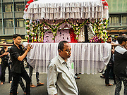 23 OCTOBER 2015 - YANGON, MYANMAR: Men carry a coffin representing Hussein ibn Ali through the streets of Yangon during an Ashura procession. Ashura commemorates the death of Hussein ibn Ali, the grandson of the Prophet Muhammed, in the 7th century. Hussein ibn Ali is considered by Shia Muslims to be the third imam and the rightful successor of Muhammed. He was killed at the Battle of Karbala in 610 CE on the 10th day of Muharram, the first month of the Islamic calendar. According to Myanmar government statistics, only about 4% of the population is Muslim. Many Muslims have fled Myanmar in recent years because of violence directed against Burmese Muslims by Buddhist nationalists.    PHOTO BY JACK KURTZ