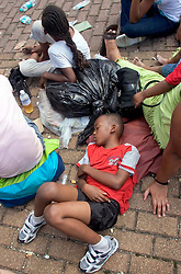 31st August, 2005. 'Hell on earth.' A child lies on the bricks at the Superdome in New Orleans, Louisiana where over 20,000 refugees from hurricane Katrina are crammed into hellish conditions.