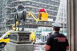 A police officer for Police Scotland waits for a quiet word with Ricky McConnell who dressed as Santa and waved at passeres by from the Duke of Wellington on the statue in Royal Exchange Square Glasgow<br />  21 December 2015<br />  Copyright Paul David Drabble<br />  www.pauldaviddrabble.co.uk