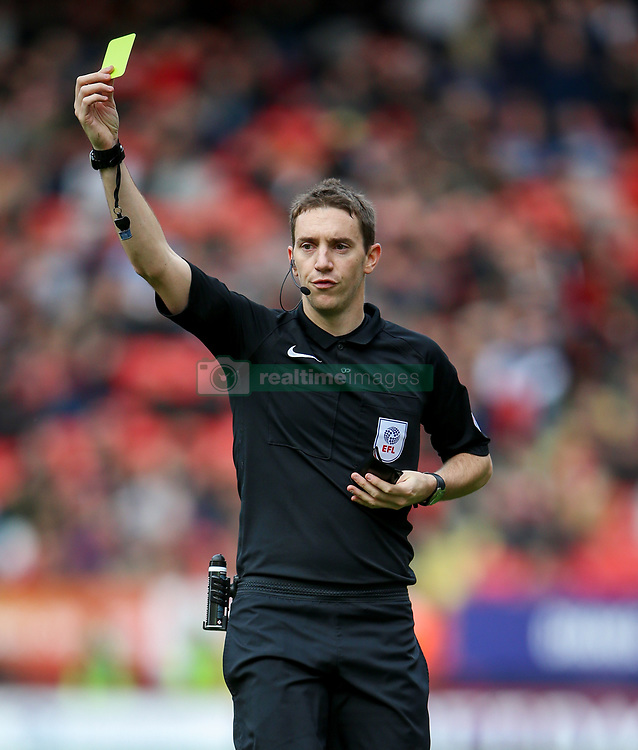 Referee Ben Toner brandishes a yellow card