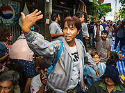 03 SEPTEMBER 2016 - BANGKOK, THAILAND: Protestors call for reinforcements as Bangkok city officials storm into the Pom Mahakan community. Hundreds of people from the Pom Mahakan community and other communities in Bangkok barricaded themselves in the Pom Mahakan Fort to prevent Bangkok officials from tearing down the homes in the community Saturday. The city had issued eviction notices and said they would reclaim the land in the historic fort from the community. People prevented the city workers from getting into the fort. After negotiations with community leaders, Bangkok officials were allowed to tear down 12 homes that had either been abandoned or whose owners had agreed to move. The remaining 44 families who live in the fort have vowed to stay.      PHOTO BY JACK KURTZ