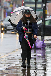 © Licensed to London News Pictures. 09/10/2020. London, UK. A woman shelters from the rain underneath an umbrella in north London. According to the Met Office more rain is forecast for the weekend. Photo credit: Dinendra Haria/LNP