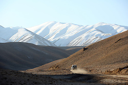 NCA  vehicles navigate hazardous roads over mountain passes to reach a village that is part of the project area. Daikundi, Afghanistan.