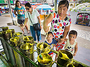 20 JULY 2015 - NONTHABURI, NONTHABURI, THAILAND:  A woman and her sons put wax into a candle mold for the Rains Retreat (also called Buddhist Lent) on Nonthaburi Pier, the end of the Chao Phraya Express Boat line in Nonthaburi, a suburb of Bangkok. This is the north end of a plan to develop the Chao Phraya River riverfront. The Chao Phraya promenade is development project of parks, walkways and recreational areas on the Chao Phraya River between Pin Klao and Phra Nang Klao Bridges. The 14 kilometer long promenade will cost approximately 14 billion Baht (407 million US Dollars). The project involves the forced eviction of more than 200 communities of people who live along the river, a dozen riverfront  temples, several schools, and privately-owned piers on both sides of the Chao Phraya River. Construction is scheduled on the project is scheduled to start in early 2016. There has been very little public input on the planned redevelopment.          PHOTO BY JACK KURTZ
