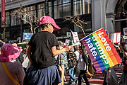 """San Francisco, USA. 19th January, 2019. A child sits on shoulders watching the Women's March San Francisco  while holding a rainbow flag reading: """"Love trumps hate."""" Credit: Shelly Rivoli/Alamy Live News"""