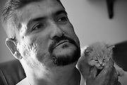 Carlos watches TV with his new kitten 'Sugar'.  Carlos Raposa, 47, has lived with diabetes since he was 21.  Mr. Raposa had both legs amputated from the knees down due to complications from the disease.  Mr Raposa lives in Fall River and visits his mother regularly who lives close by.  She cooks for him and helps him deal with the cripling condition he has been dealing with.  As his condition has worstened over the years Carlos has had greater difficulty dealing with his condition.  Increasingly, Carlos has fallen greater into depression and has turned to smoking and drinking to deal with it.  What used to be monthly visits to the hospital has turned into weekly excursions with ever longer stays in hospital.  Family members have become ever more worried about Carlos' drop in weight and his inability to move on his own any longer.  For someone who was an athletic figure, Carlos has become a shadow of his former self.