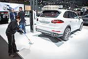 New York, NY, USA-23 March 2016. A woman polishing the display floor in Porsche's stand at the New York International Auto Show. Cleaning staff were continually at work, polishing floors, dusting cars, and cleaning glass. Shown is a Porsche hybrid Cayenne S.