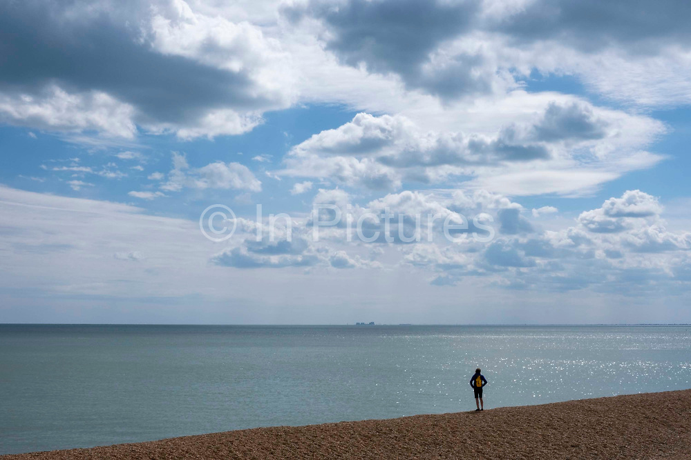 A person stands alone on Folkestone seafront looking out across Hythe Bay toward Dungeness Power station on the 4th of June 2020, Folkestone, United Kingdom.