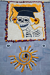 North America, Mexico, San Miguel de Allende, courtyard of Universidad de Leon, skeleton graduate made of beans with marigolds at altar for Day of the Dead  celebration, also known as Dios de los Muertos.  Mexicans celebrate the Day of the Dead on November 1st and 2nd in connection with the Catholic holy days of All Saints' Day and All Souls' Day.