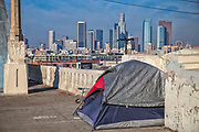 Tent of homeless person on 6th Street Bridge with Los Angeles skyline in the background. California, USA