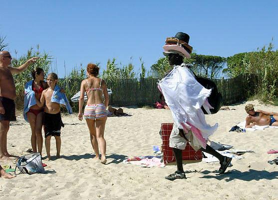 Frankrijk, St. Tropez, 9-9-2006....Op de stranden bij Saint-Tropez proberen Fransen van Afrikaanse herkomst wat te verdienen met de verkoop van hoeden, badhanddoeken en jurkjes aan de badgasten. Tijdens de zomermaanden lopen zij de Zuid-Franse stranden af om in de winter naar hun land van herkomst te gaan. Met het verdiende geld ondersteunen zij veelal hun familie in Afrika.....Foto: Flip Franssen/Hollandse Hoogte