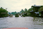 River traffic boats passing wooden houses on waterway near Bankgkok, Thailand in 1964