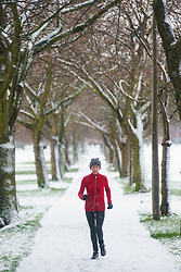 Edinburgh, Scotland, UK. 31 December 2020. A woman running along tree lined footpath in The Meadows park in Edinburgh during a morning snowfall today. Iain Masterton/Alamy Live News