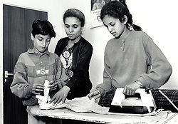 Children helping mother with the ironing, Forest Fields, Nottingham UK 1990