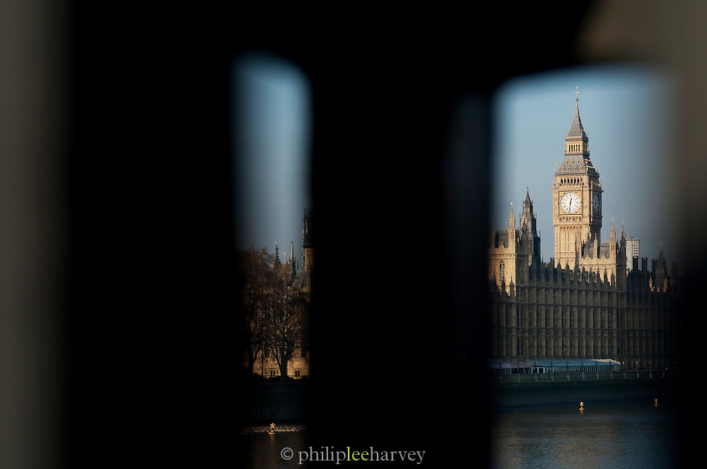 The Houses of Parliament and Big Ben on the River Thames seen through a bridge gap, London, UK