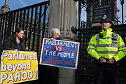 On the day that the EU in Brussels agreed in principle to extend Brexit until 31st January 2020 (aka 'Flextension') and not 31st October 2019, a Brexiter's stands next to a police officer beneath the railings outside parliament with a placard warning of a confrontation between the People and Parliament, on 28th October 2019, in Westminster, London, England.