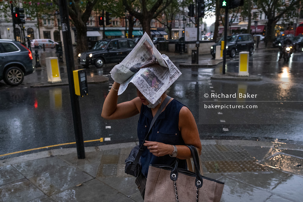 During an early evening downpour in Sloane Square, a lady covers her head with the latest edition of the Evening Standard newspaper, on 24th August 2020, in London, England.