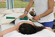 young Female receiving a Soothing relaxing massage by male therapist with the aid of a MagCreator by Nikken said to have special therapeutical magnetic powers
