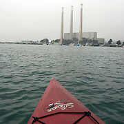 The well known smoke stacks from the Morro Bay Power Plant rise above Morro Bay as seen from a kayak.