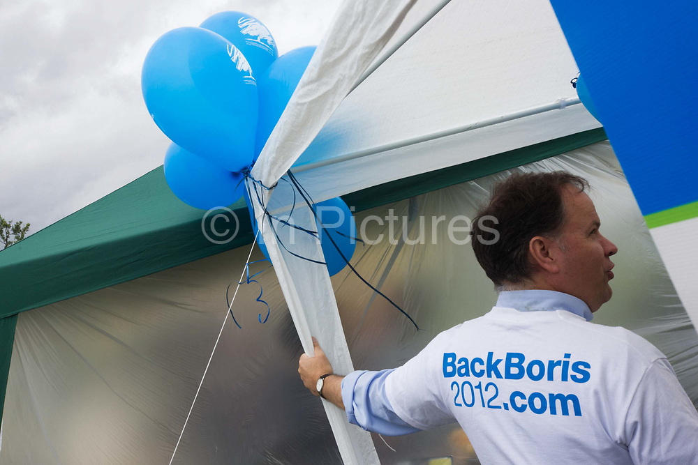 A Conservative Party's volunteer wears a Back Boris Johnson for London mayor campaign at the Lambeth Fair in Brockwell Park. At a white marquee the worker mans a tent at the annual south London country show where a mix of society come to enjoy a community fair where political lobbying meets nature, entertainment and world food. The current London Mayor is the Tory Boris Johnson, (a university friend of Prime Minister David Cameron) who is seeking re-election in Olympic year, 2012. The 2012 London mayoral election will be held on Thursday 3 May 2012 to elect the Mayor of London. It will be the fourth such election since the post of Mayor of London was started in 2000.