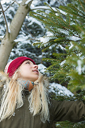 Teenage girl looking up on fir tree in forest in winter, Bavaria, Germany