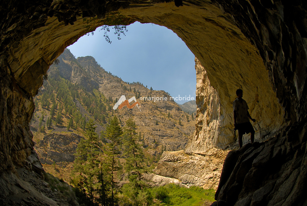 Man silhouetted while enjoying pictographs in Veil Falls on the Middle Fork of the Salmon River, Idaho.