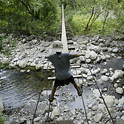 A young boy navigates an old, swinging bridge with missing planks on the island of Maui.