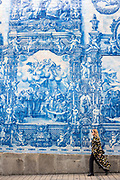 Stylish woman passes azulejos Portuguese blue and white ceramic wall tiles of Capela das Almas de Santa Catarina  - St Catherine's Chapel in Porto, Portugal