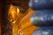 09 MARCH 2009 -- BANGKOK, THAILAND: The reclining Buddha statue at Wat Po in Bangkok. Wat Phra Chetuphon is more commonly known by its old name of Wat Po. The temple is much older than the city of Bangkok itself. It was founded in the 17th century, making it the oldest temple in Bangkok. The name Wat Po comes from its original name of Wat Potaram. King Rama I, the founder of Bangkok, enlarged the temple, installed many statues and other artefacts recovered from Ayuthaya, and renamed the temple Wat Phra Chetuphon in 1801. Rama III enlarged the temple in 1832 and turned the temple into a center of learning, making it in essence Thailand's first university. Rama III is also responsible for the construction of the reclining Buddha, which the temple is famous for.   Photo By Jack Kurtz