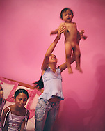 14 year old Roma girl Garoafa Mihai, a few weeks prior to her wedding, throws her younger brother Mario up in the air whilst her sisters watch, in her parent's home in the village of Sintesti, in Romania, early August 2006.  The Kalderari roma of Sintesti are by tradition metal workers, originally making alcohol stills, pots and pans, but now dealing in scrap metal. The large profits from their business have enabled them to build large houses in the village of Sintesti, 20km from Bucharest, and to invest in fast, Western brand name cars such as BMW's, Mercedes and Porsche.