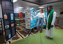 © Licensed to London News Pictures; 23/09/2021; Bristol, UK. MIA SMITH from Bristol Energy Network demonstrates LED lighting to ABDUL RAHEEM, Imam at the Easton Jamia Mosque, at an exhibition on climate change inside the Mosque. The  Mosque has created a booklet, A Muslim's Guide to Climate Change. The booklet, authored by Abdul Malik Chairman of the Easton Jamia Mosque is thought to be the first in the UK. The Mosque has an exhibition as part of a day of action to unite the local community for a common cause, to understand human causes of climate change and to campaign and take action against climate change. The event is part of a national initiative called the Great Big Green Week with more than 4,500 events, organised by environmental charities collectively known as The Climate Coalition. Photo credit: Simon Chapman/LNP.